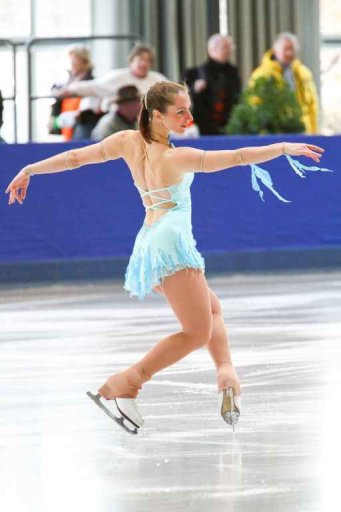 CP on the ice, arms stretched out, balancing on the toes, audience blurred in the background