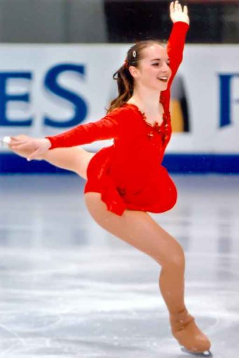 CP on the ice, smiling on the landing of a jump